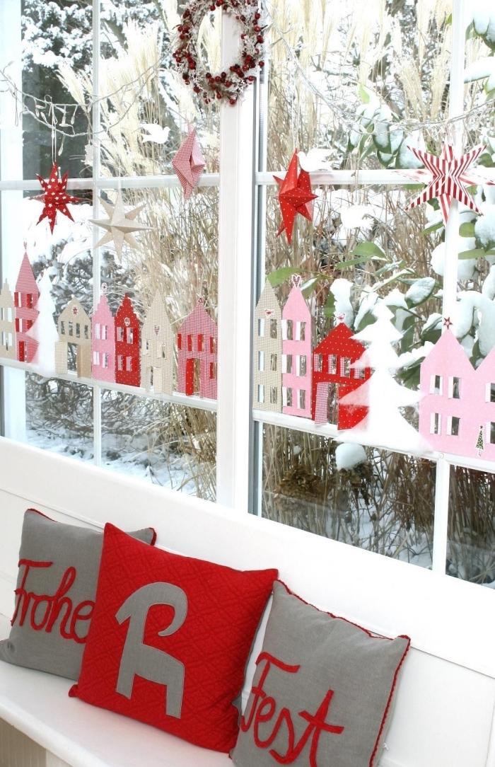 de petites silhouettes de maisons découpées en papier rose et rouge pour décorer la vitre à Noëln guirlande d'étoiles en papier suspendue à la fenêtre en dessus un banc blanc