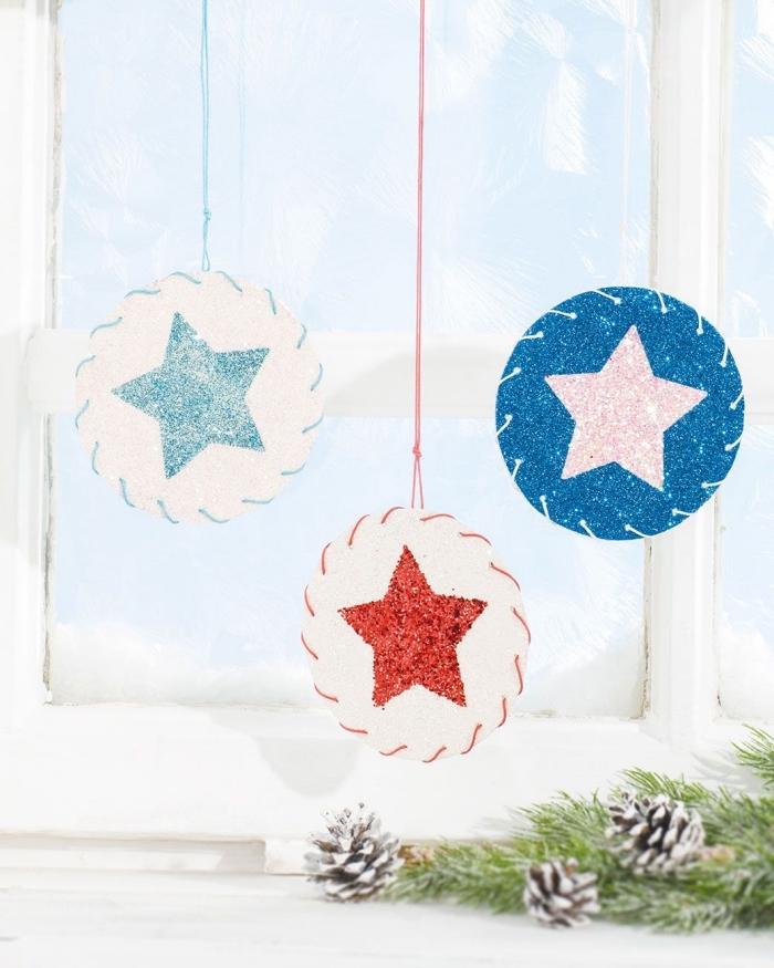 idée de décoration de noel à fabriquer en papier, des suspensions de noël en ronds de papier à motif étoile pailletée suspendues à la fenêtre