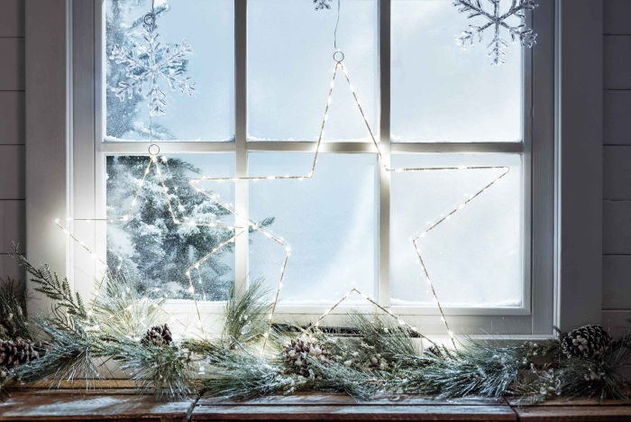 une étoile lumineuse et une guirlande verte de branches de sapin posées sur le rebord de la fenêtre, deco de noel a faire soi meme