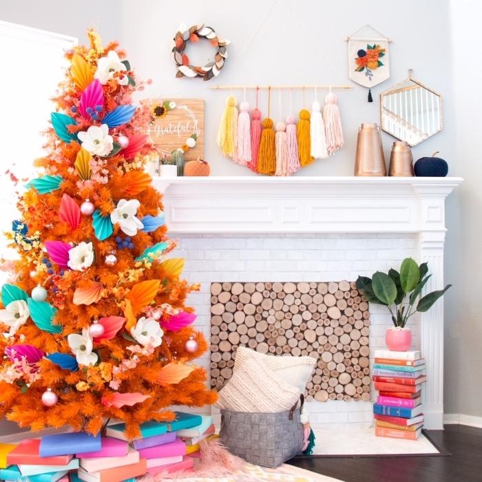 sapin de noel artificiel de luxe en couleur orange décoré de fleurs et de feuilles en papier coloré sur un pied d'un tas de livres qui s'harmonise avec l'ambiance joyeuse et bohème chic du salon