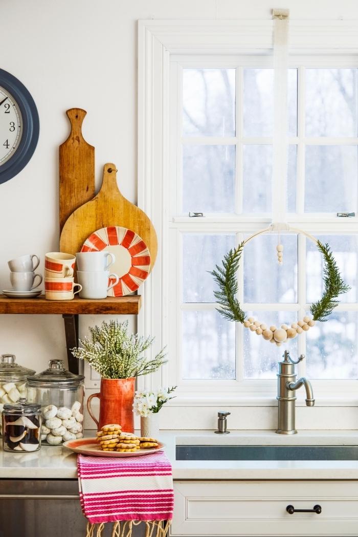 décoration de cuisine pour noël avec une simple couronne réalisée en cerceau de bois, perles de bois et quelques brins de sapin, suspendue à la fenêtre derrière l'évier