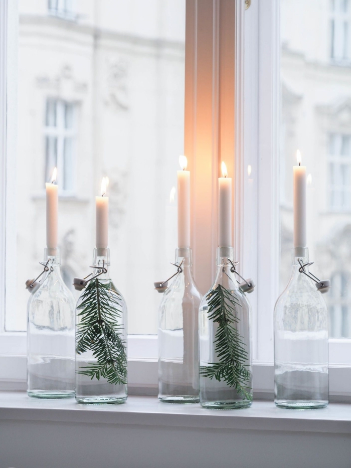 décorer le rebord de la fenêtre avec des bougeoirs en bouteilles en verre vintage, deco de noel a fabriquer soi même avec des matériaux de récup
