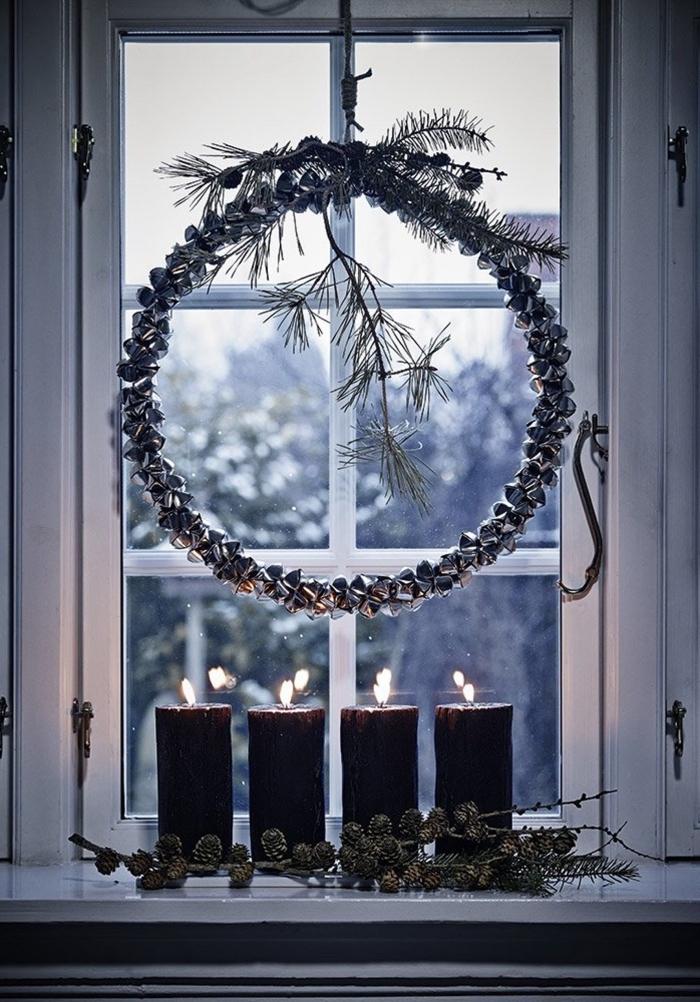 décoration de fenêtre de noël traditionnelle avec une couronne de noël suspendue et des bougeoirs en bois