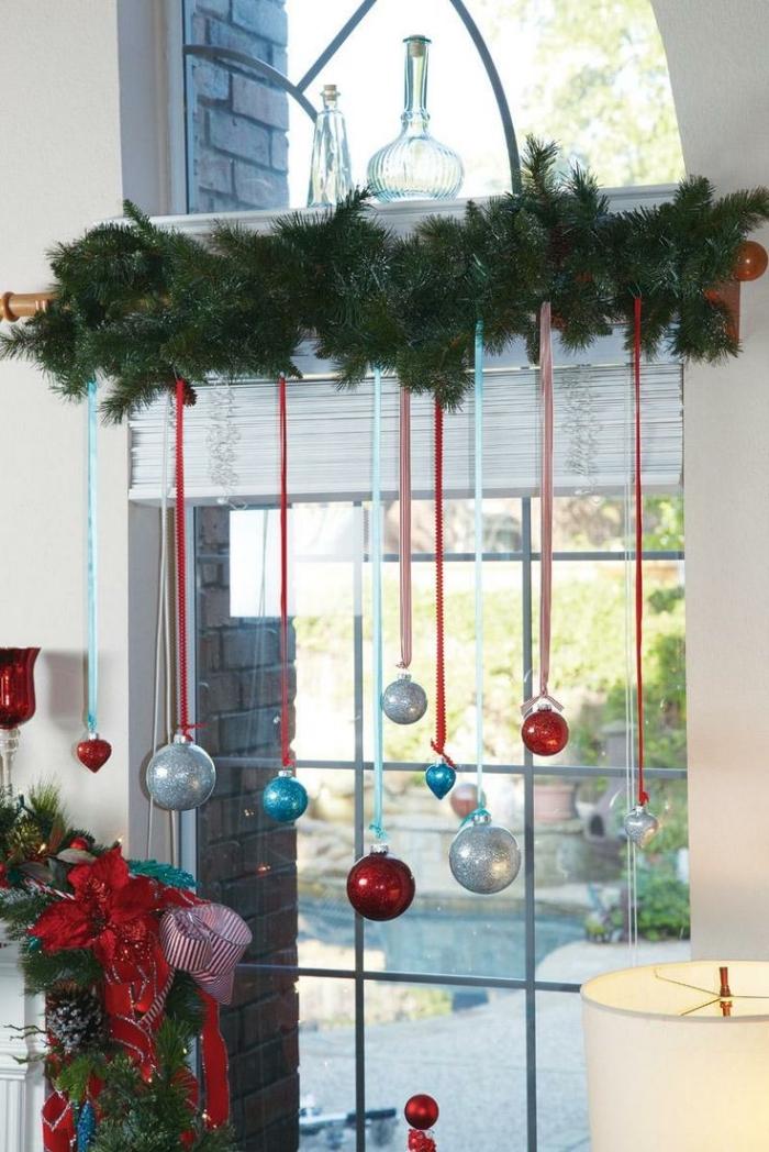 une guirlande verte de branche de sapin agrémentée de quelques suspensions de noël avec boules, fixée à la tringle à rideaux, deco de noel a faire soi meme pour animer les fenêtres
