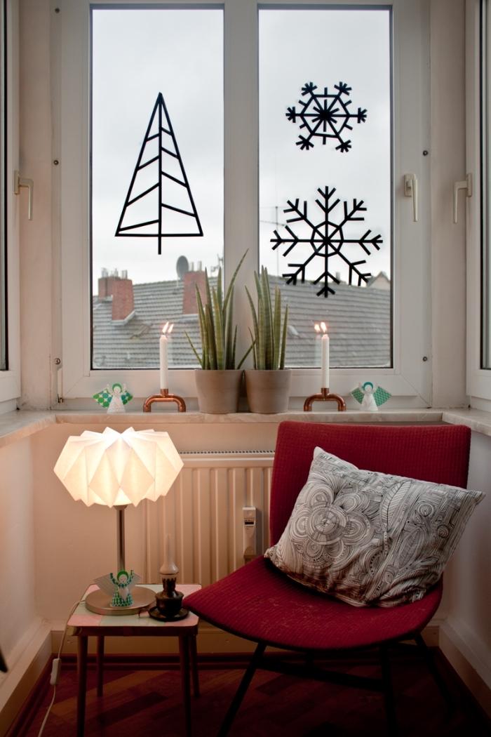 décorer les vitres avec un sapin de noël original et des flocons de neige en masking tape, coin de lecture décoré pour l'hiver avec un fauteuil rouge et une petite table d'appoint illuminée par une lampe à poser origami