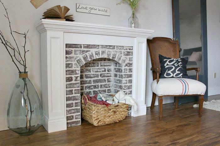 meuble mural imitation cheminée avec manteau blanc et faux foyer en fausses briques pour déco de salon retro cosy rustique