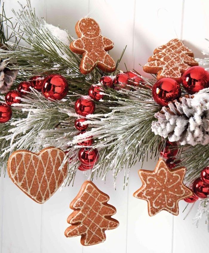 peitit gateau de noel pain d épice pour decorer une brache de pin décorée de boules de noel rouges, neige artificielle