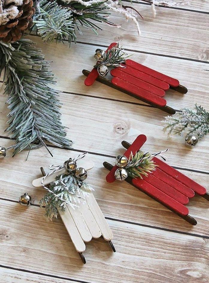 petit traineau en batonnets de glace rouge et sans couleur avec deco branches de pin et clochettes, décoration de Noël à fabriquer pour adultes