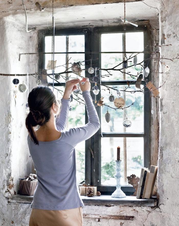 décoration de noel à fabriquer en bois, une branche nue suspendue à l'horizontale et agrémenté d'ornements de noël pour créer une déco de fenêtre originale pour l'hiver