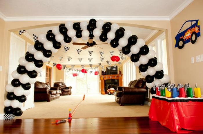 salle de séjour, arche en ballons noirs et blancs, tapis beiges, canapés en cuir, paquets colorés avec cadeaux, cheminée