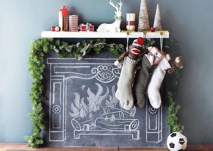 ardoise avec dessin imitation cheminée à la craie sur mur comme faux feu décoratif avec guirlande de noel et objets déco chaussettes suspendues