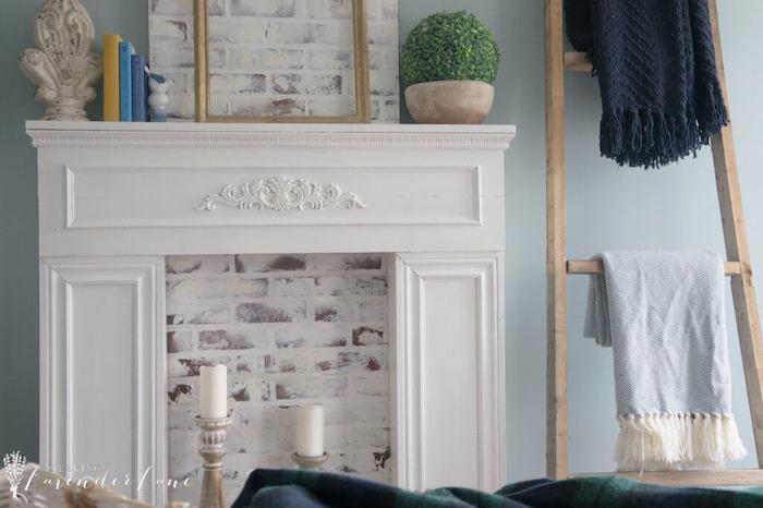 deco fausse cheminée blanche avec fond en briques fausses sur mur bleu ciel et echelle deco en bois