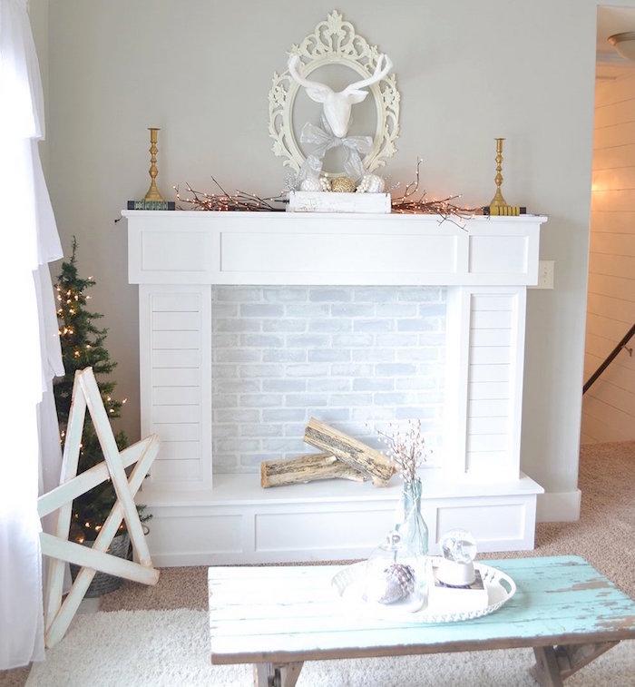 meuble imitation cheminée blanc pour décoration de salon cosy sur mur gris et sol moquette avec petite table en bois patine retro