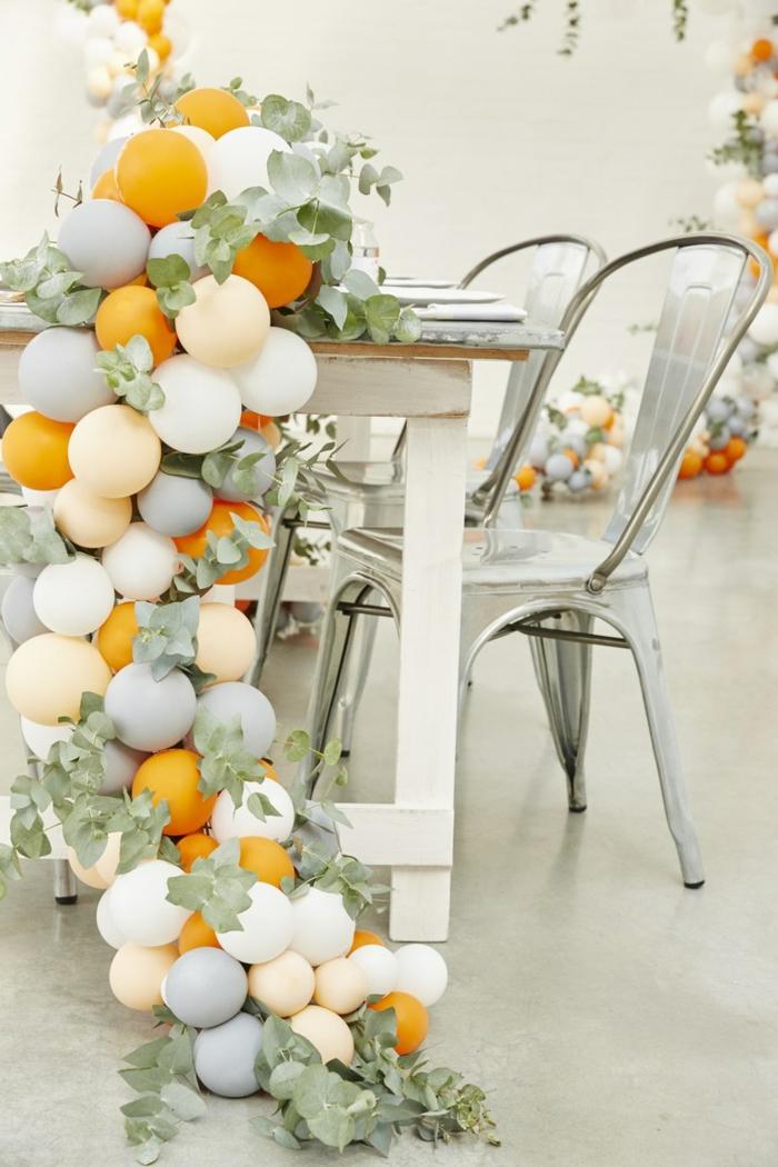 chaises tolix, ballons blancs et jaunes avec feuilles en grande arche faite avec ballons, intérieur blanc