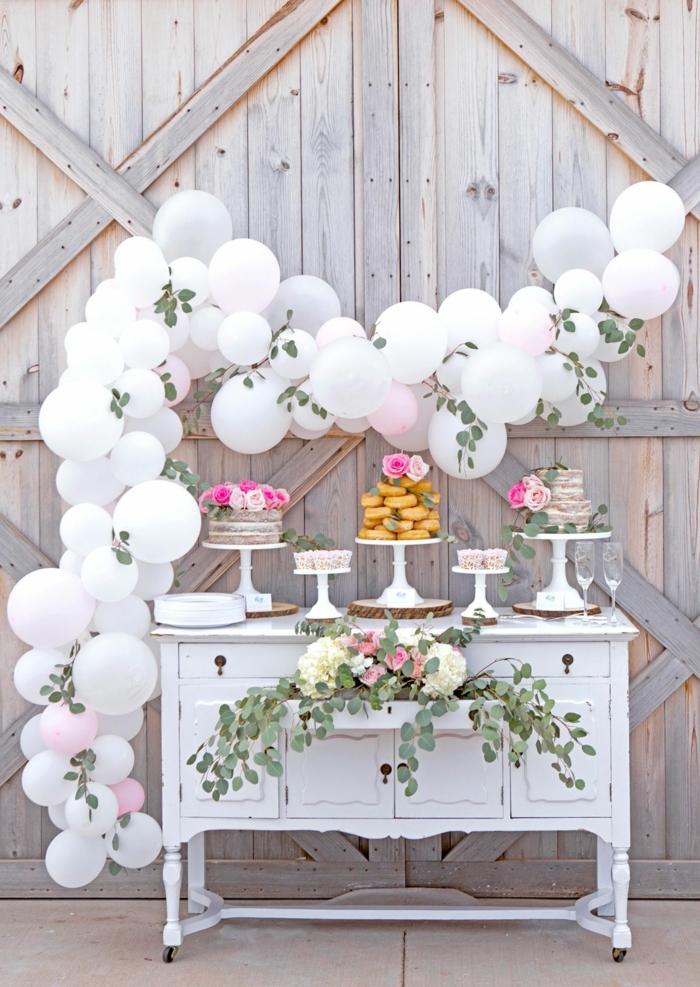 arche de ballons blancs, feuilles vertes, présentoir à gâteau, arche mariage blanche, gâteau et donuts