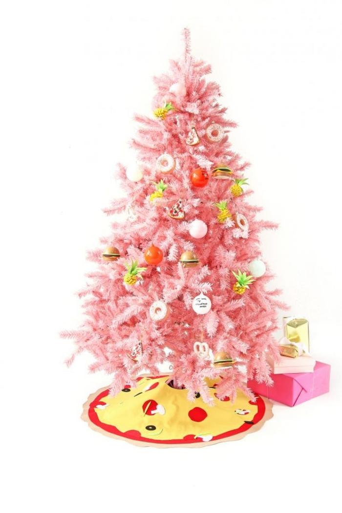 un joli sapin de noel artificiel de luxe en rose pastel orné de suspensions originales et insolites ananas, donuts et boules de noël, avec un couvre-pied original imitant un pizza