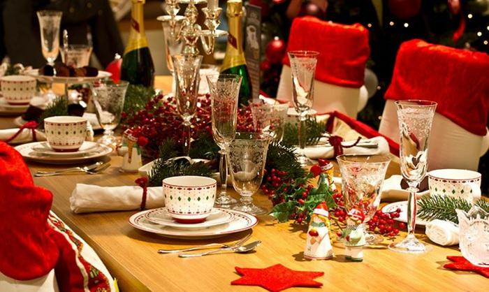 deco table noel a fabriquer tasses  caf  serviettes blanches enroul es chaises aux dossiers rouges  toiles rouges centre de table baies rouges et branches de pin