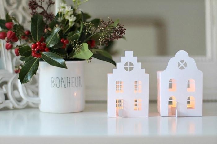 deux maisons lumineuses découpées en papier pour décorer une table ou une étagère pour noël, fabriquer deco noel avec des photophores faits maison