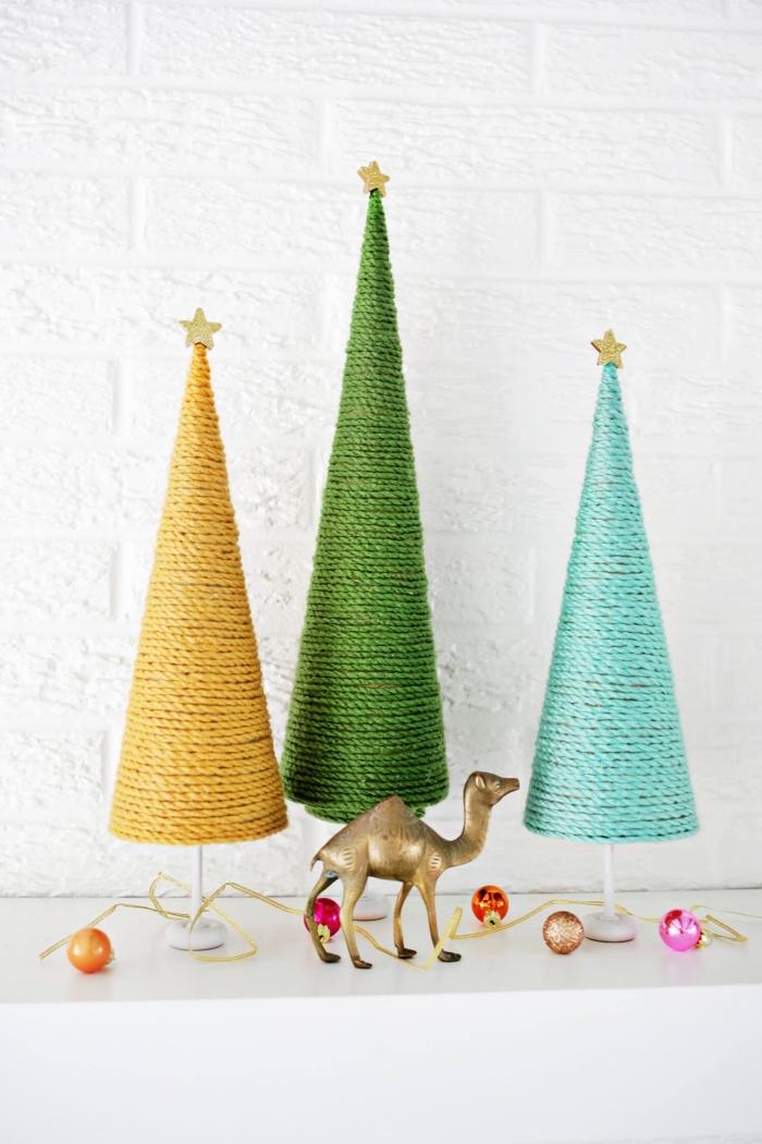 une décoration de noël originale et colorée à faire soi-même, des mini-sains de noël en cônes de papier habillés de fils de laine colorés