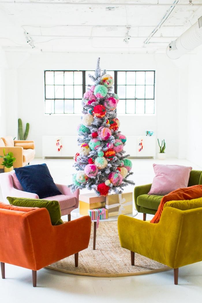 sapin de noel artificiel de luxe orné de gros pompons en laine multicolores, qui trône au centre d'un salon vintage bohème chic