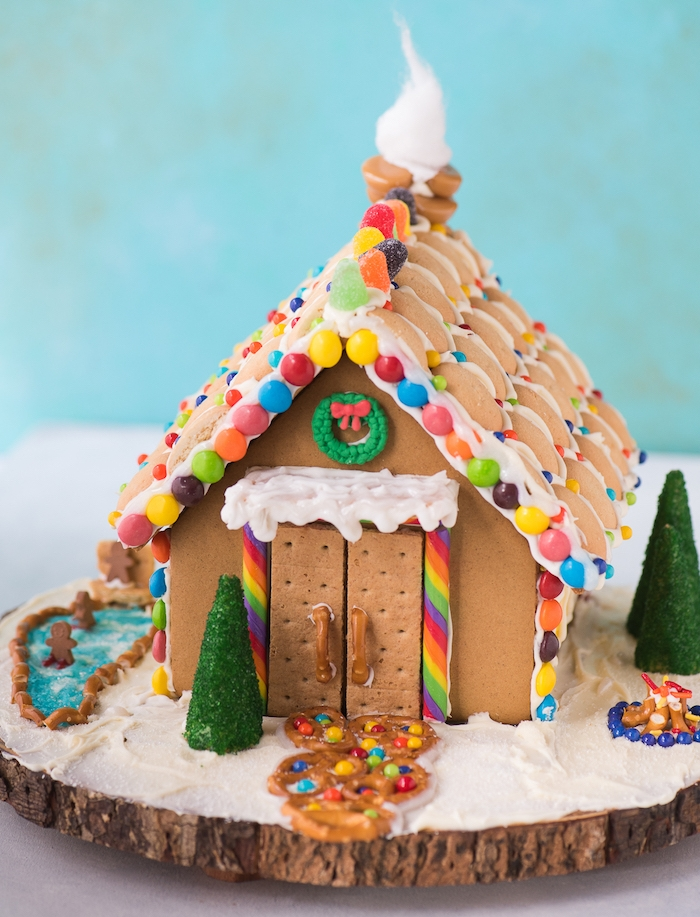 decoration de noel gourmand, dessert de noel original maison pain d épice avec deco de biscuits, bonbons colorés, bretzels et autres sur un rondin de bois