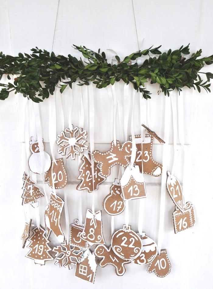 calendrier de l avent personnalisé en branche verte avec des figurines en papier cartonné suspendu contours blancs, motifs boule de noel, flacon de neige, chaussette, sapin de noel