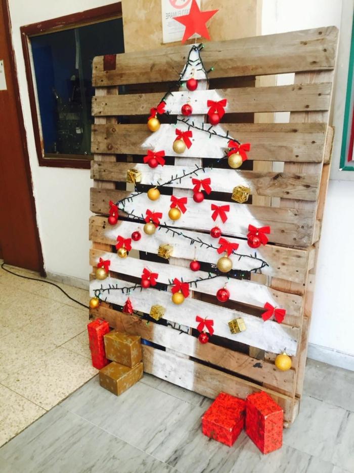palette en bois avec silhouette de sapin blanche, rubans, ornements, étoile rouge, cadeaux rouges et dorés