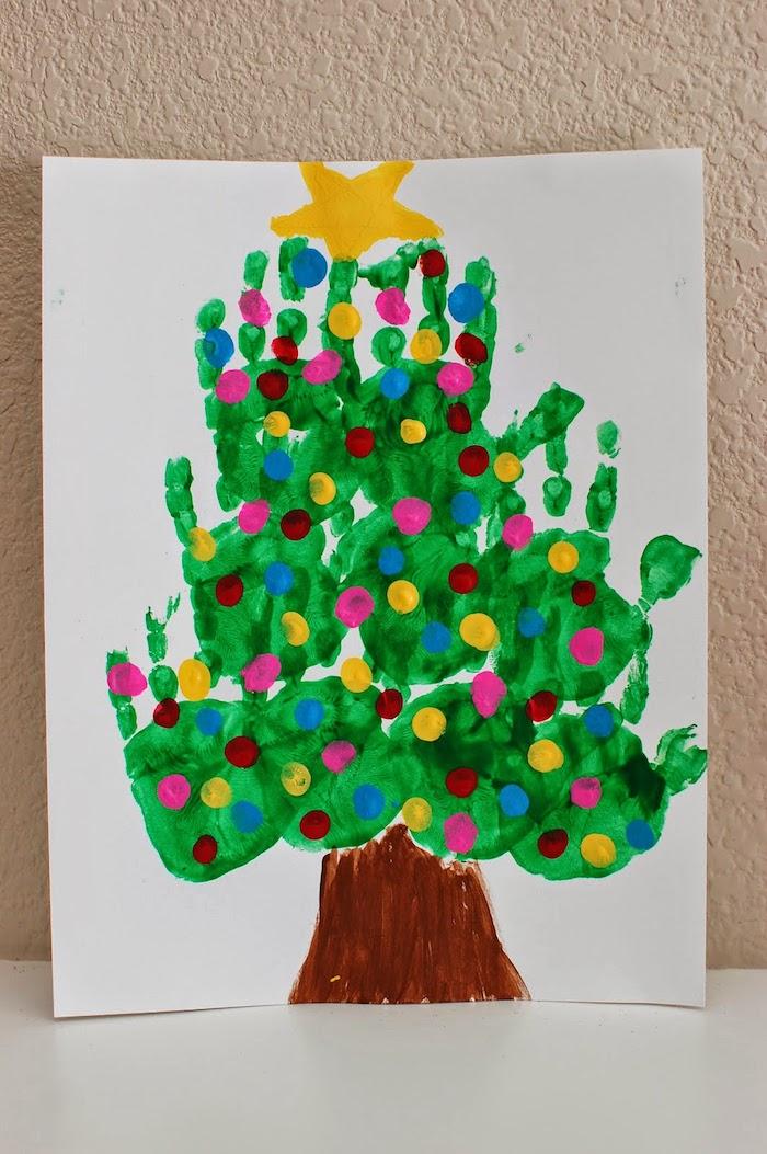 sapin de noel en empreintes de main couleur verte avec une étoile de peinture en top, tronc peinture marron, activité manuelle noel maternelle
