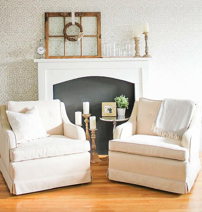 photo salon déco minimaliste avec cheminée décorative à fond noir et objets déco rétro, fauteuils en tissu clair, sol parquet et tapisserie gris blanc