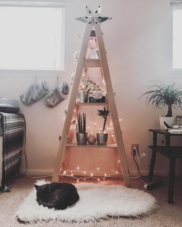 une échelle en bois transformée en sapin de noël original décorée d'une guirlande lumineuse et d'objets déco en tons argentés