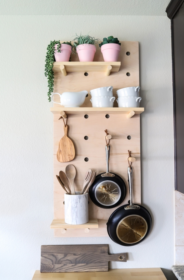 astuce rangement cuisine pout optimiser l'espace vertical de la cuisine, un tableau en bois perforé mural avec des étagères et des bâtons de bois pour y ranger ses ustensiles de cuisine