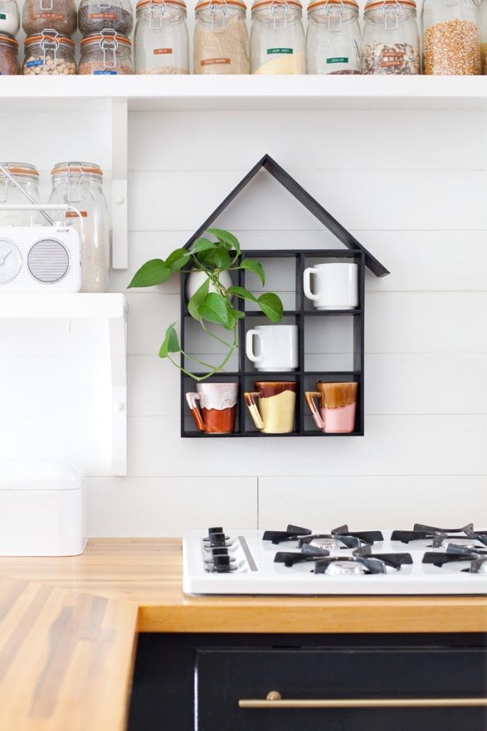 une étagère en forme de maison peinte en noir qui accueille toutes nos tasses favorites, suspendu au mur derrière la cuisinière