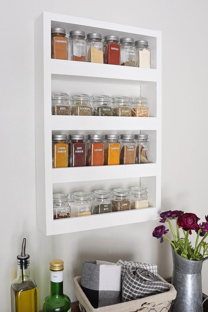 un rangement épices blanc installé au mur, étagère murale à quatre niveaux pour y ranger de petits pots à épices