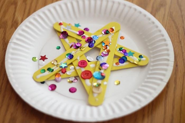 étoile de noel en batonnets de glace colorés de peinture jaune avec deco de strass, boutons collés dessus, bricolage noel maternelle