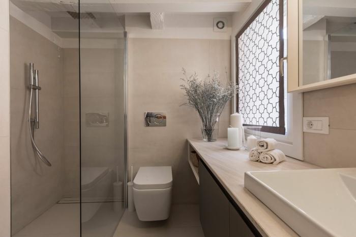 salle d'eau couleur grège, toilette blanche, plateau beige lisse, vasque rectangulaire en pente, serviettes enroulées, fenêtre avec panneau décoratif