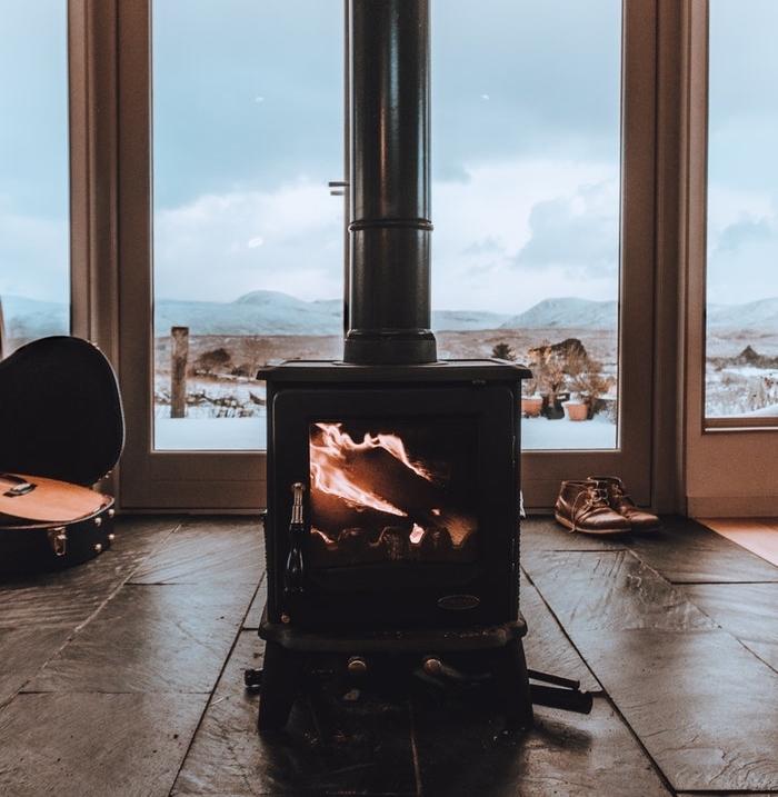exemple de cheminée moderne noire au milieu d un salon style rustique, gros vitres et paysage enneigé sur le fond