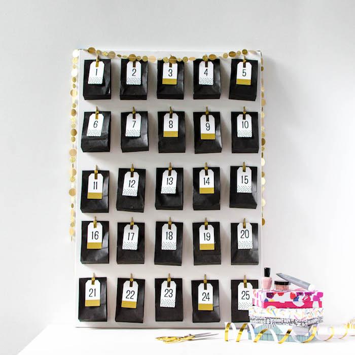 calendrier de l avent beauté original en sachets noirs avec des étiquettes cadeau aux chiffres collées sur un panneau blanc accroché à un mur