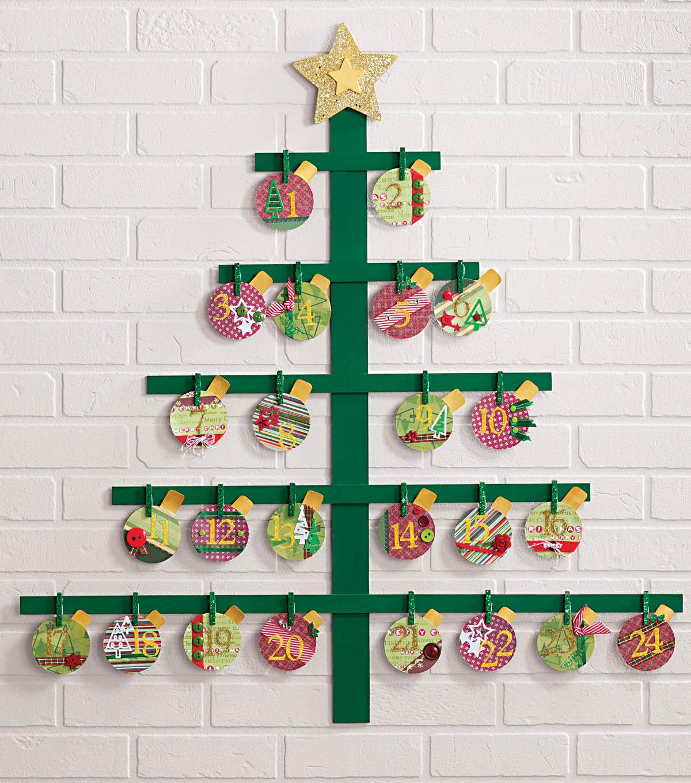 fabrication calendrier de l avent en planches de bois repeintes de vert avec des boules de noel colorés accrochées à des pinces à linge sur un mur de briques