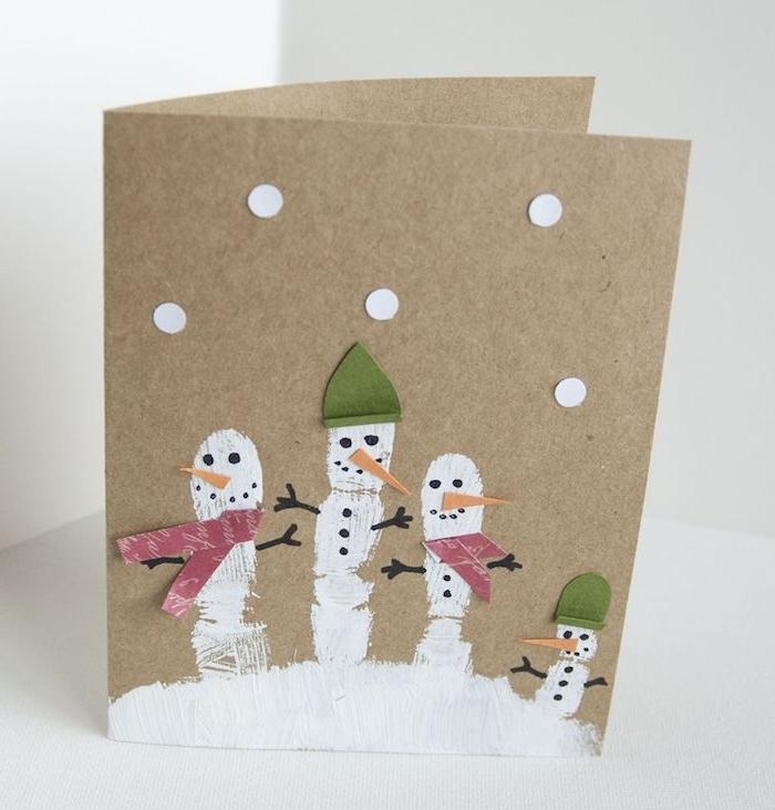 empreintes de doigts en peinture blanches sur du papier kraft, petits bonhommes de neige scrapbooking, bricolage primaire carte de noel