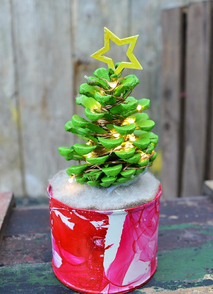 deco de noel a faire soi meme avec recup, pomme de pin repeintes de peinture verte avec guirlande lumineuse et étoile bois jaune