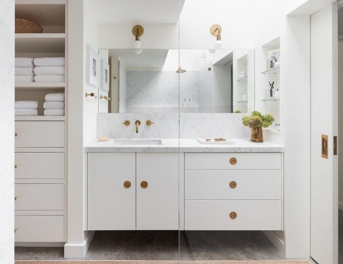 meuble salle de bain moderne avec armoires et tiroirs blancs à poignées dorées, déco stylée en marbre et or