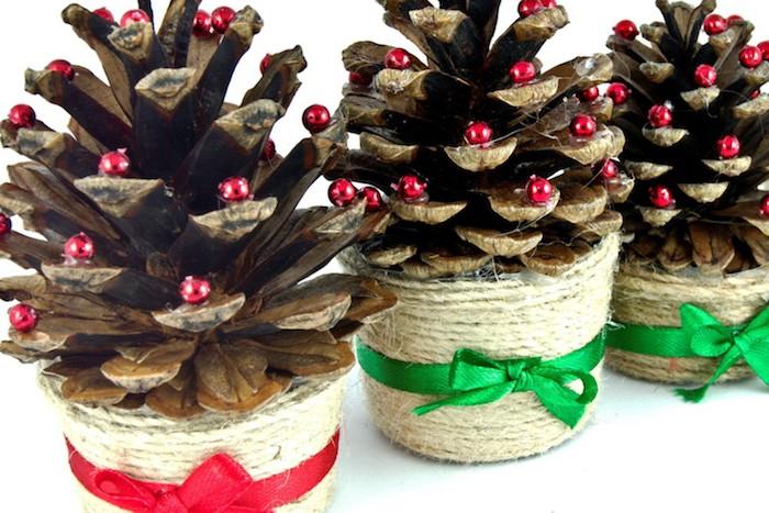 petit sapin de noel en pomme de pin décoré de petites perles rouges dans un pot en verre décoré de fils de chanvre et ruban rouge et vert