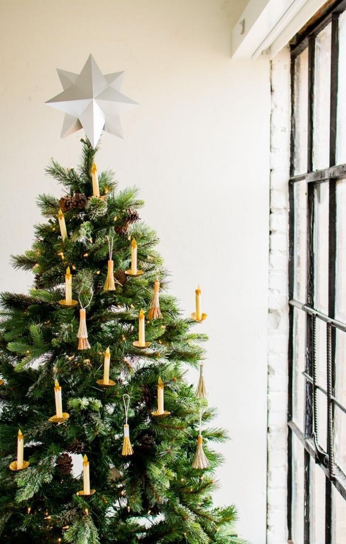 décoration de sapin de noël naturel avec des ornements en papier en forme de bougies dorées et un joli cimier étoile origami