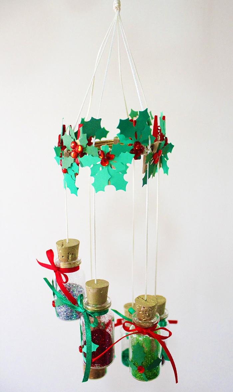mobile de noel à suspendre au plafon en fioles remplies de paillettes et couronne de pierres et feuilles de papier imitation houx