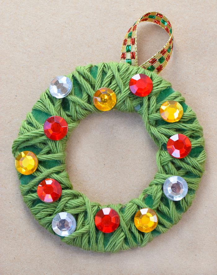 couronne de noel diy miniature en cercle de papier décoré de fil vert enroulé autour et strass à accrocher sur un sapin de noel