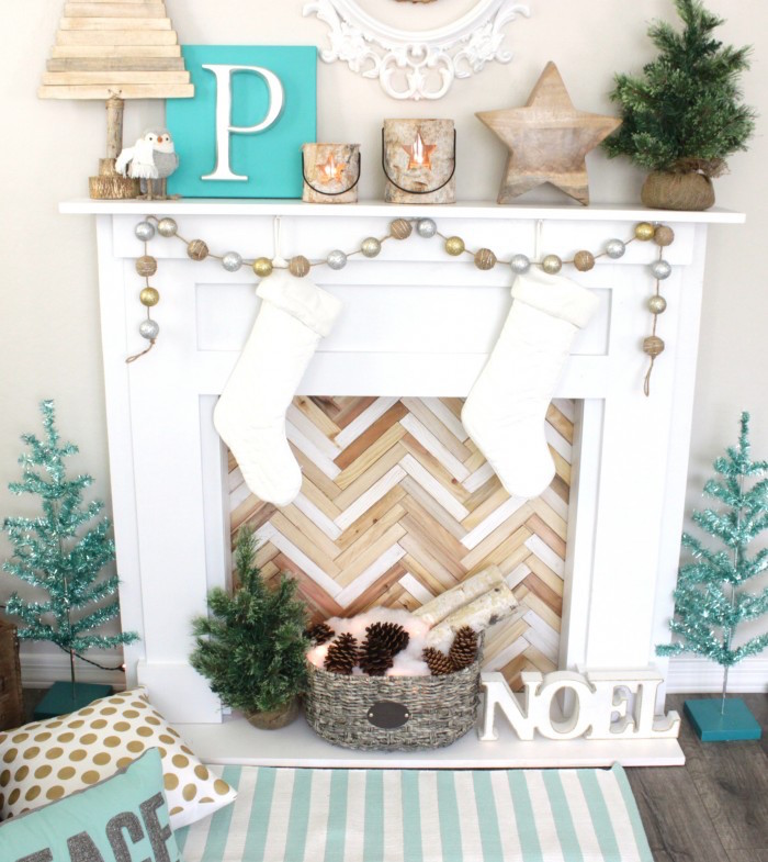 fausse cheminée avec manteau en bois blanc avec décoration de noel avec objets déco en bois blanc et turquoise