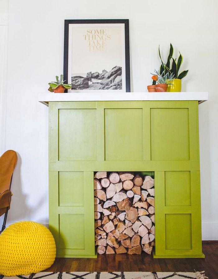 faux manteau cheminée décorative vert pomme sur mur blanc avec stock buches dans insert sur parquet bois ciré et petits pots de cactus