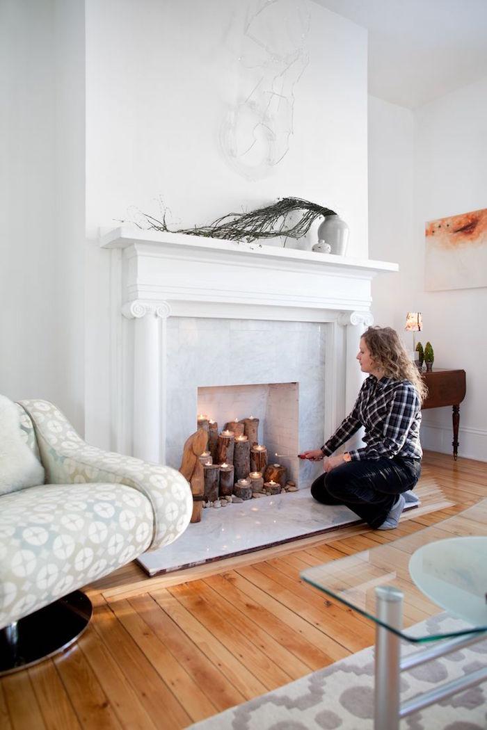 faux manteau de cheminée condamnée avec mini biches bougies dans foyer marbre dans salon blanc scandinave sur sol en parquet