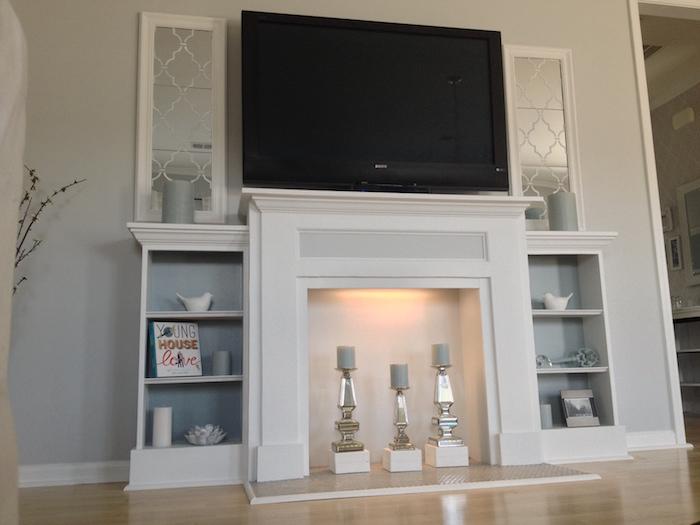 manteau de fausse cheminée comme support tv avec rangements sur les cotés sur mur blanc sur sol parquet clair et bougies grises dans insert