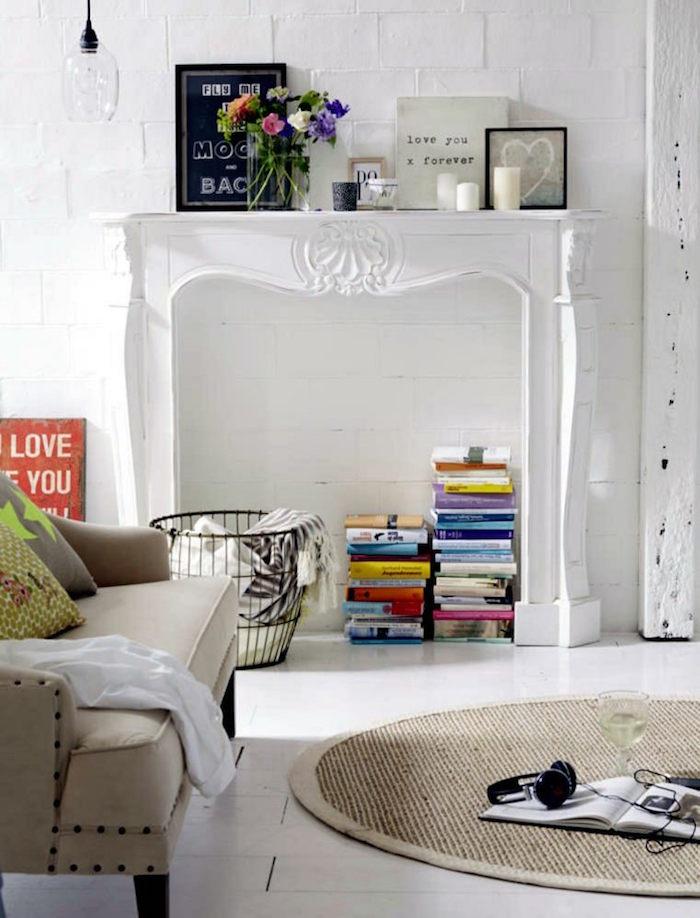 manteau cadre de cheminée blanc en bois pour décoration de salon sur mur en pierres blanches avec livres déco dans l'insert et cadres photo pour une ambiance scandinave